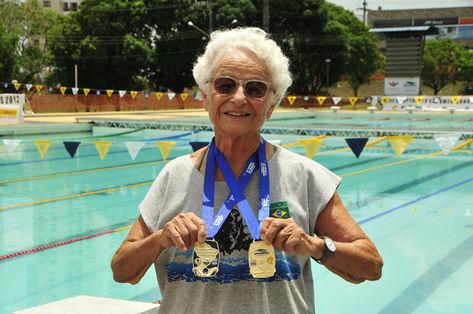 A campeã exibindo as muitas medalhas que já conquistou na natação