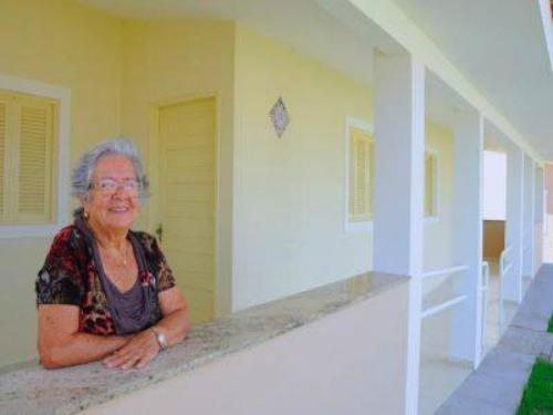 Uma idosa na área externa da casa